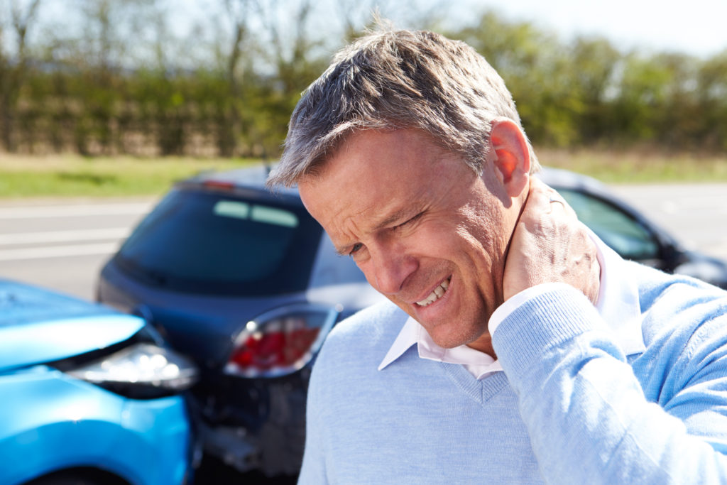 Man holding the back of his neck after an auto accident suffering from whiplash
